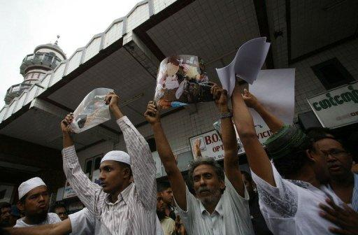 Myanmar Muslims hold up pictures of recent violence in Rakhine state during a gathering in Yangon on June 5. Myanmar's reformist government has launched an official probe into a flare-up of sectarian violence in the west of the country, state media said, pledging to punish those responsible