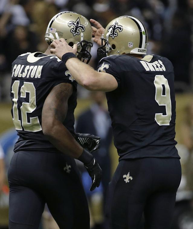 New Orleans Saints wide receiver Marques Colston (12) celebrates his touchdown reception with quarterback Drew Brees (9) during an NFL football game in New Orleans, Sunday, Dec. 8, 2013. (AP Photo/Dave Martin)