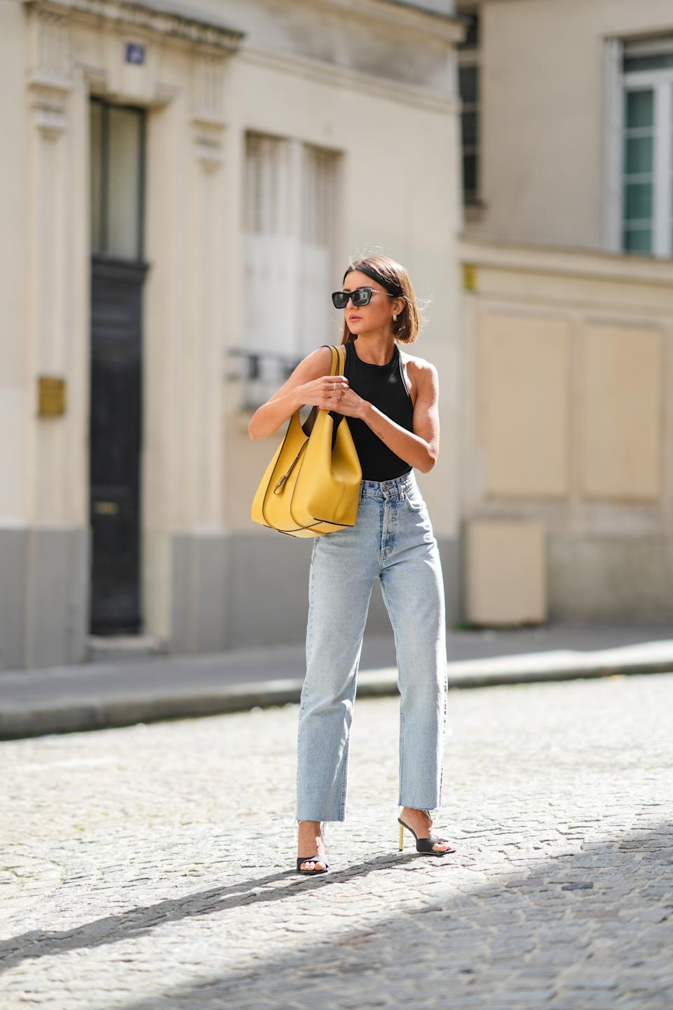 PARIS, FRANCE - AUGUST 27: Alexandra Pereira wears black sunglasses, gold earrings, a black ribbed halter-neck cropped t-shirt, blue faded denim high waist ripped flared jeans pants, a large yellow shiny leather shoulder bag from Tods, black suede open toe-cap pumps heels shoes with gold heels, silver rings, on August 27, 2021 in Paris, France. (Photo by Edward Berthelot/Getty Images)
