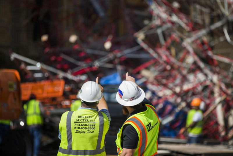 Construction workers begin cleaning up collapsed scaffolding on the 300 block of East Martin Street, Friday, Sept. 20, 2019 in San Antonio. Officials say three bystanders were slightly hurt as a 100-foot (30-meter) section of scaffolding collapsed on a San Antonio street amid 50 mph (80 kph) winds from a system linked to Tropical Storm Imelda. The scaffolding, along a high-rise building, crushed several parked vehicles and crashed into St. Mark's Episcopal Church. (Daniel Carde/The San Antonio Express-News via AP)