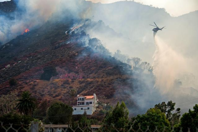 <p>A helicopter drops water to protect a home at the Holy Fire in Lake Elsinore, California, southeast of Los Angeles on Aug. 10, 2018. (Photo: Robyn Beck/AFP/Getty Images) </p>