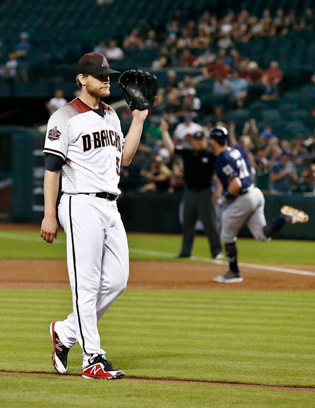 Arizona Diamondbacks starting pitcher Matt Koch, left, waits for a new baseball after giving up a two-run home run to Milwaukee Brewers' Travis Shaw, right, during the first inning of a baseball game Wednesday, May 16, 2018, in Phoenix. (AP Photo/Ross D. Franklin)