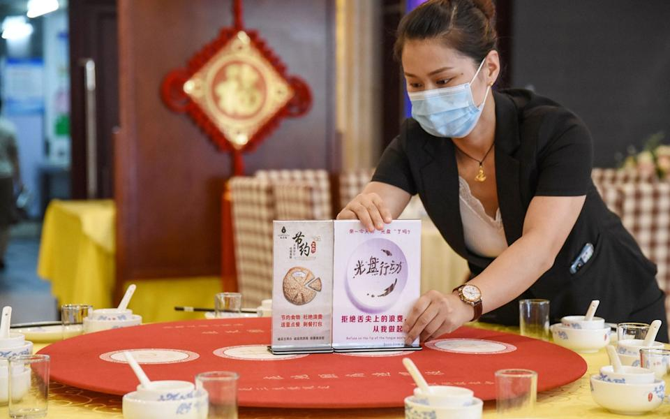 A staff member sets up signs encouraging people not to waste food at a restaurant in Handan - STR/AFP