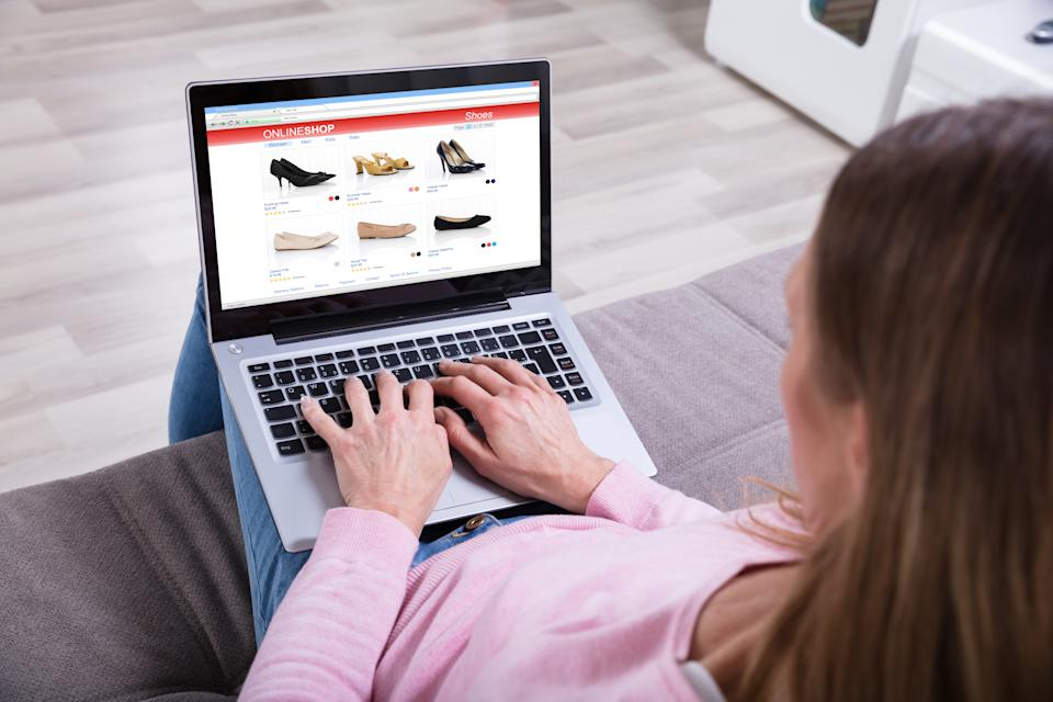 Close-up Of Woman Sitting On Sofa Shopping Footwear's Online On Laptop At Home