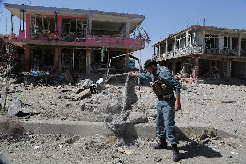 An Afghan policeman inspects the site of a suicide attack in Ghazni, eastern Afghanistan on September 4, 2014 (AFP Photo/Rahmatullah Alizadah)