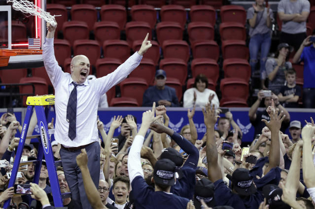 Utah State head coach Craig Smith twirls a cut-down net after his team's upset of San Diego State in the Mountain West title game. (AP Photo/Isaac Brekken)