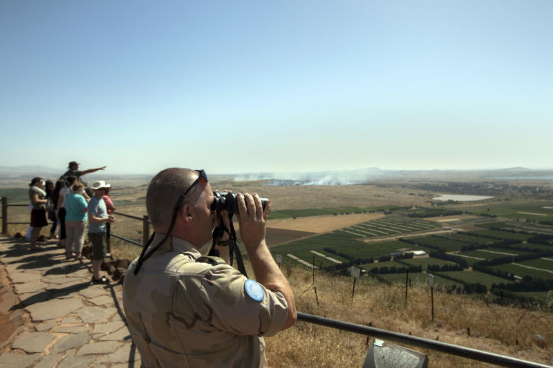 A UN soldier looks through binoculars towards Syria from an observation point on Mt. Bental in the Golan Heights, near the border between the Israeli-controlled Golan Heights and Syria, Friday, June 7, 2013. Syrian rebels on Thursday briefly captured a crossing point along a cease-fire line with Israel in the contested Golan Heights. (AP Photo/Sebastian Scheiner)
