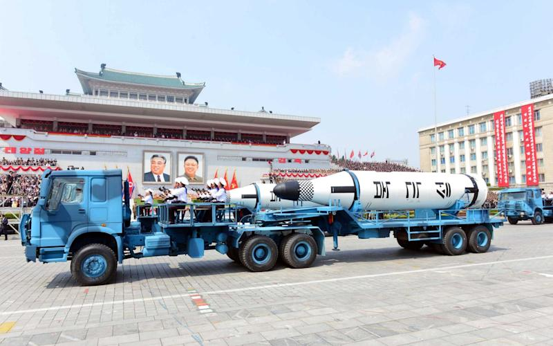 Chinese made military vehicles carry missiles with characters reading