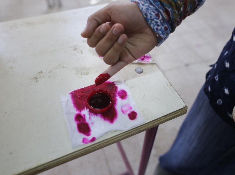 A voter dips her finger in ink during the first day of three-day voting on constitutional amendments in Cairo, Egypt, Saturday, April 20, 2019. Egyptians are voting on constitutional amendments that would allow el-Sissi to stay in power until 2030. (AP Photo/Amr Nabil)