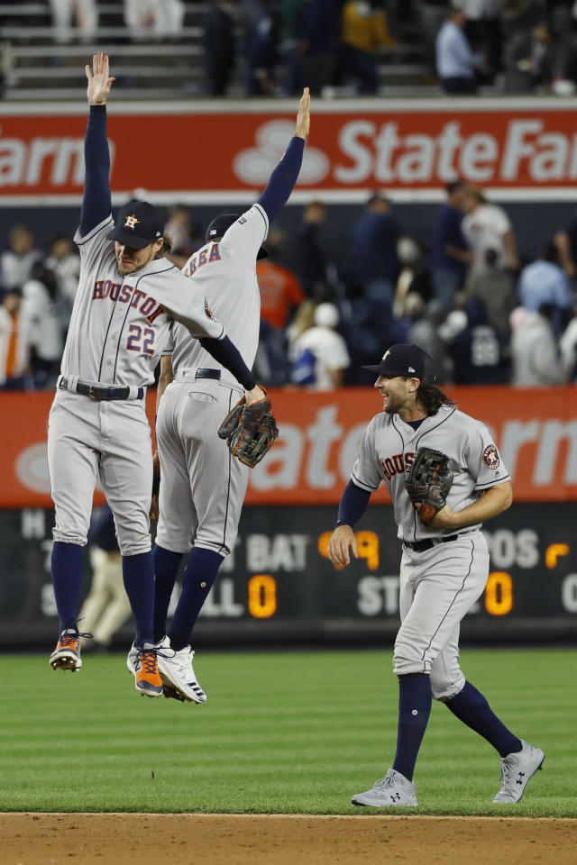 Houston Astros right fielder Josh Reddick, left, shortstop Carlos Correa and center fielder Jake Marisnick celebrate after their 4-1 win against the New York Yankees in Game 3 of baseball's American League Championship Series Tuesday, Oct. 15, 2019, in New York. (AP Photo/Matt Slocum)