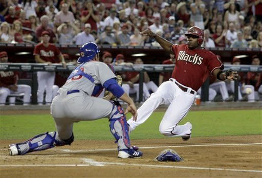 Arizona Diamondbacks' Justin Upton, right, slides home safely in the first inning in front of Chicago Cubs catcher Anthony Recker during a baseball game Sunday, Sept. 30, 2012, in Phoenix. (AP Photo/Rick Scuteri)