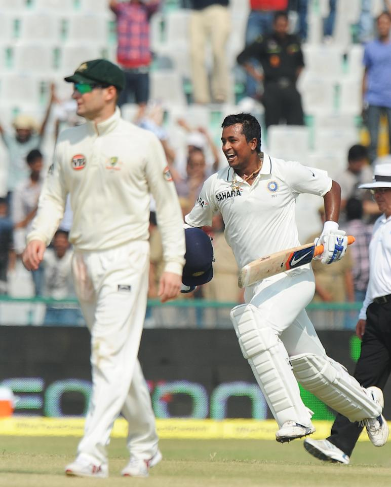 Indian cricketer Pragyan Ojha runs behind Australian cricketer Michael Clarke as he celebrate India's win over Australia during the final day of the first Test between India and Australia in Mohali on October 5, 2010. India beat Australia by one wicket on the fifth and final day of the opening Test to gain a 1-0 lead in the two-match series. AFP PHOTO / Dibyangshu SARKAR (Photo credit should read DIBYANGSHU SARKAR/AFP/Getty Images)