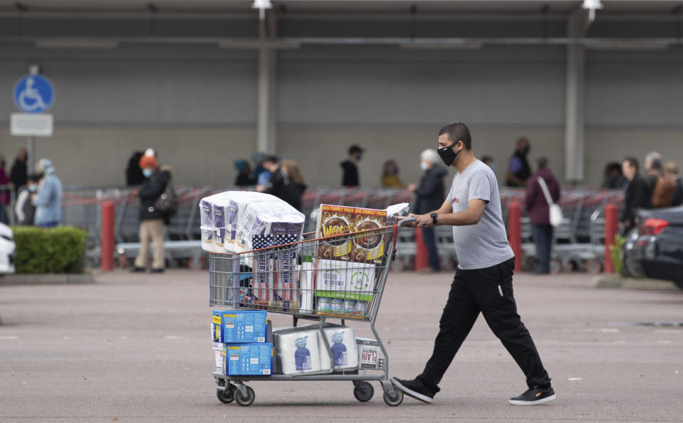 One shopper walks away with a full cart as others queue outside a major supermarket in Leicester, England, Sunday Nov. 1, 2020. The British government announced on Saturday a four-week public lockdown in response to the latest coronavirus surge, and government lawmaker Michael Gove on Sunday acknowledged that the lockdown could be extended. (Joe Giddens/PA via AP)