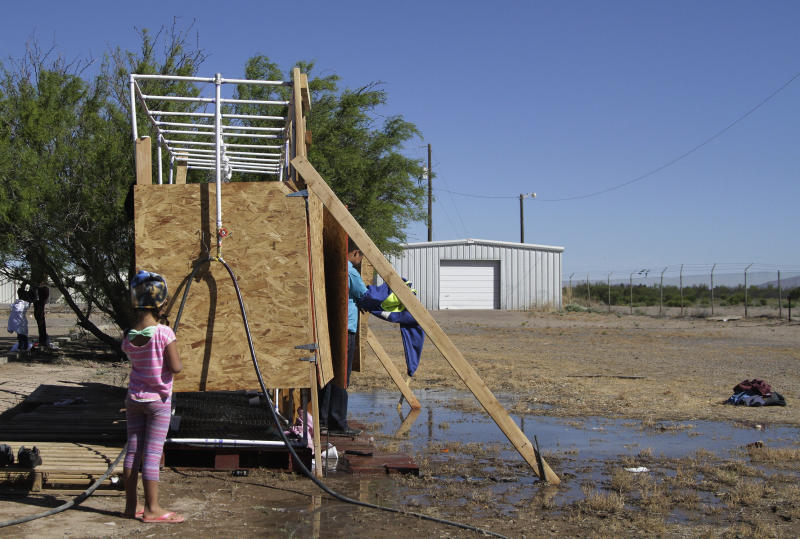 CORRECTS DAY - In this Wednesday, May 22, 2019, Migrants wait for a turn at a cold shower in a shelter set up by city officials in Deming, N.M. A surge of asylum-seeking families has been straining cities along the southern U.S. border for months, but now the issue is flowing into cities far from Mexico, where immigrants are being housed in an airplane hangar and rodeo fairgrounds and local authorities are struggling to keep up with the influx. (AP Photo/Cedar Attanasio)