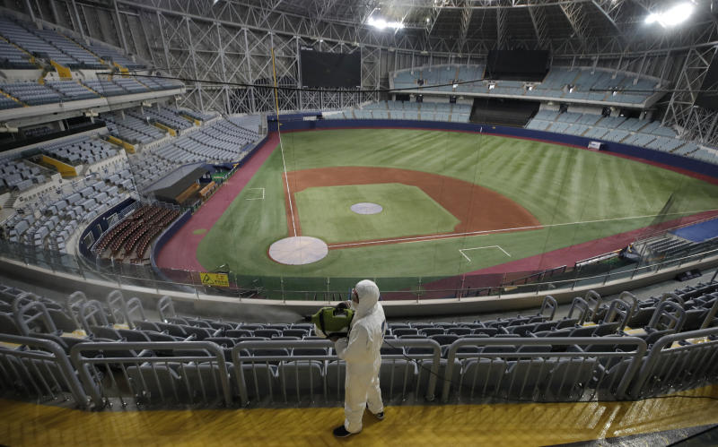 FILE - In this March 17, 2020 file photo, a worker wearing protective gears disinfects as a precaution against the new coronavirus at Gocheok Sky Dome in Seoul, South Korea. South Korea's professional baseball league said on Tuesday, June 30, it will require fans to wear masks and to sit at least a seat apart as it prepares to bring back spectators in the coming weeks amid the coronavirus pandemic.(AP Photo/Lee Jin-man, File)