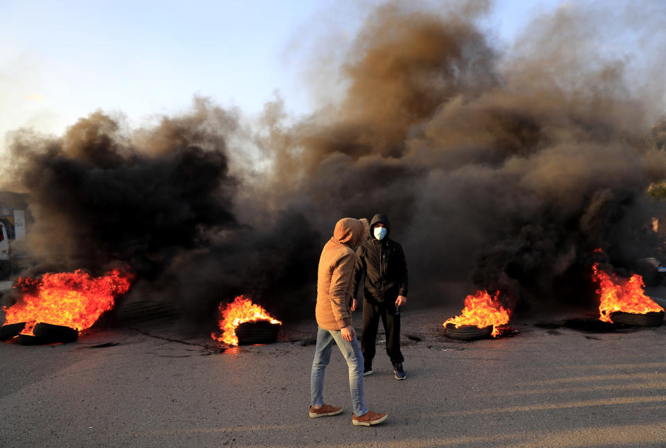 Protesters stand in front of burning tires that were set on fire to block a highway that links to the Beirut's international airport, during a protest against against the economic and financial crisis, in Beirut, Lebanon, Tuesday, March 2, 2021. The Lebanese pound has hit a record low against the dollar on the black market as the country's political crisis deepens and foreign currency reserves dwindle further. (AP Photo/Hussein Malla)