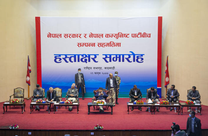 Leaders from the Nepalese government, left, and leaders of the Nepal Communist Party group sit for a signing of peace agreement, with Nepalese Prime Minister Khadga Prassad Oli seated center in Kathmandu, Nepal, Friday, March 5, 2021. leader of the group Netra Bikram Chand, who is better known by his guerrilla name Biplav, emerged out of hiding on Friday after the government lifted a ban on his group so it could take part in the public signing of the peace agreement. This group had split from the Maoist Communist party, which fought government troops between 1996 and 2006, when it gave up its armed revolt, agreed to U.N.-monitored peace talks and joined mainstream politics. (AP Photo/Niranjan Shrestha)