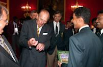 <p>The Duke of Edinburgh pulls a face while talking with Pakistan's captain and wicket keeper Kashif Mahmood (R) during a reception for the under 15 cricket teams at St James's Palace, London. The Duke was talking about getting broken fingers while playing cricket. The reception was held for the eight teams playing in the under 15 World Cricket Challenge. (Photo credit: PA/PA Archive/PA Images) </p>