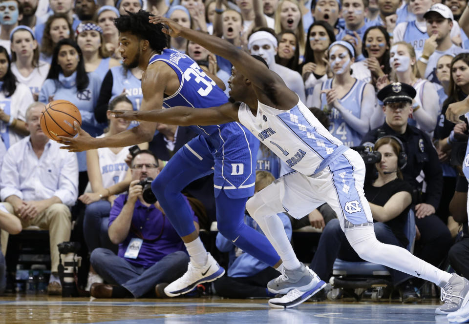 North Carolina's Theo Pinson chases the ball with Duke's Marvin Bagley III (35) during the second half of an NCAA college basketball game in Chapel Hill, N.C., Thursday, Feb. 8, 2018. North Carolina won 82-78. (AP Photo/Gerry Broome)