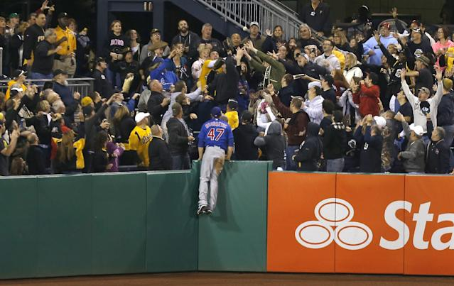 Chicago Cubs right fielder Brian Bogusevic (47) holds on to the left field wall as fans reach for a home run ball hit by Pittsburgh Pirates' Russell Martin in the fourth inning of a baseball game on Friday, Sept. 13, 2013, in Pittsburgh. (AP Photo/Keith Srakocic)