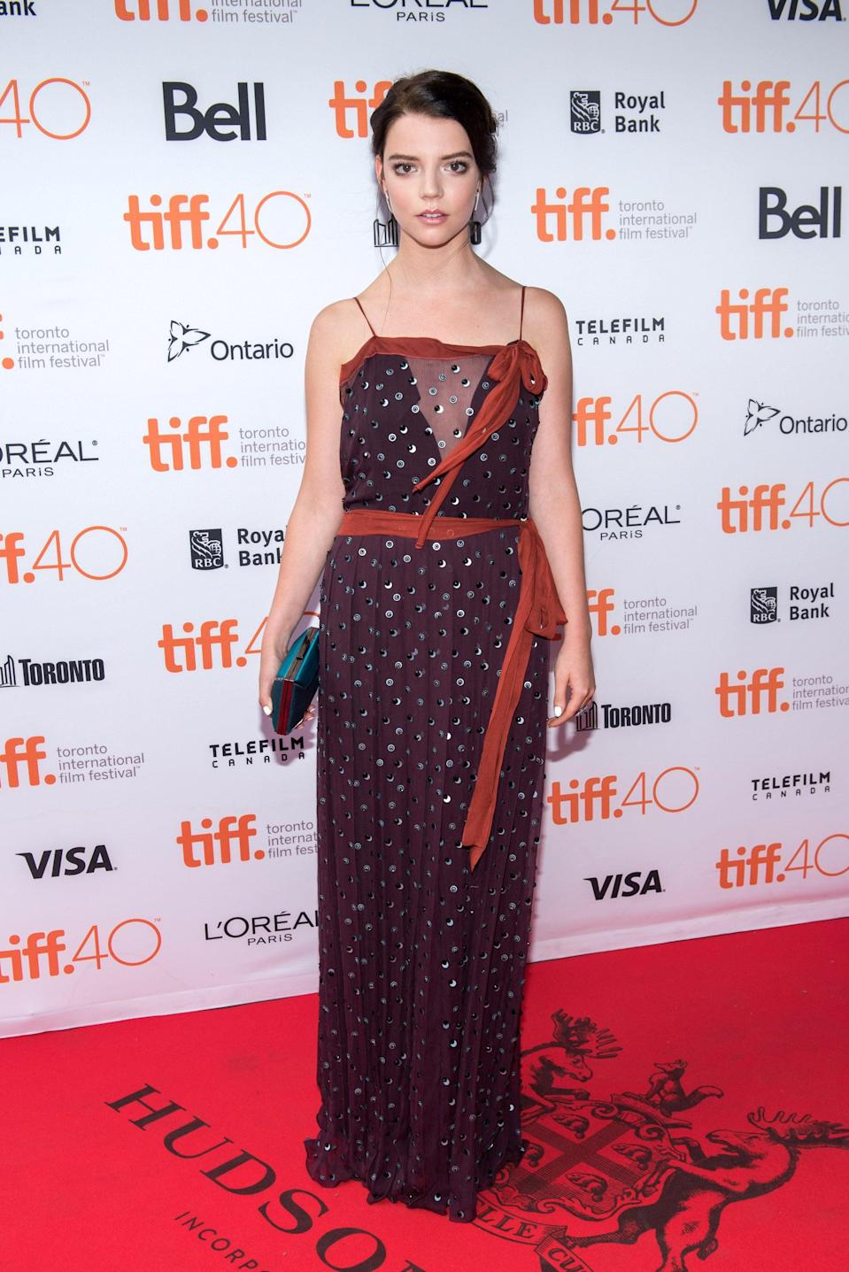 <p>Anya wore a delicate gold dot dress with red ribbon details.</p>