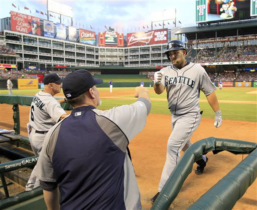 Seattle Mariners designated hitter Kendrys Morales, right, is welcomed back to the dugout by Seattle Mariners manager Eric Wedge, left, after hitting a three-run home run, his second home run of the night, during the fifth inning of a baseball game against the Texas Rangers Tuesday, July 2, 2013, in Arlington, Texas. (AP Photo/John F. Rhodes)