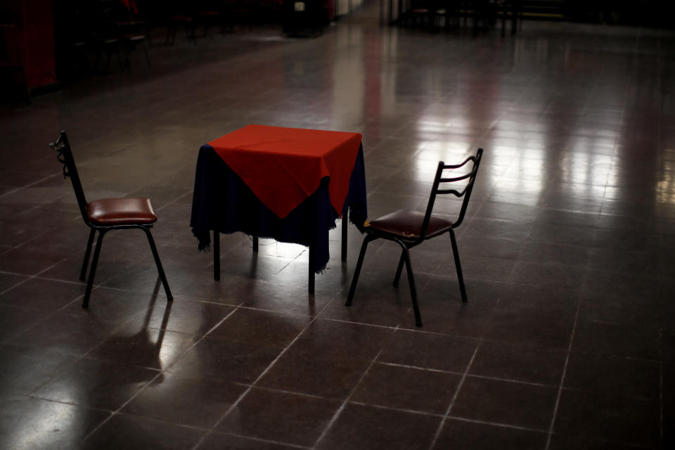 """A table and chairs sit amid the empty dance floor of La Viruta Tango club, closed during the COVID-19 pandemic lockdown in Buenos Aires, Argentina, Friday, June 4, 2021. """"For those of us who make a living from tango, our self-esteem is on the floor,"""" said Horacio Godoy, a dancer, historian and club organizer who walked across the Viruta dance hall, which recreated the atmosphere of the 1940s era when tango became a wildly popular entertainment. (AP Photo/Natacha Pisarenko)"""