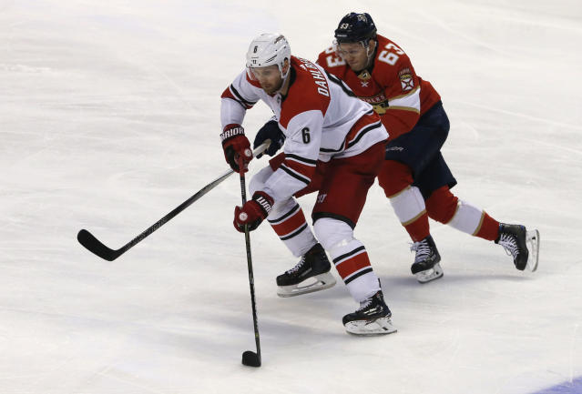 Carolina Hurricanes defenseman Klas Dahlbeck (6) battles Florida Panthers right wing Evgenii Dadonov (63) for the puck in the second period of an NHL hockey game, Monday, April 2, 2018, in Sunrise, Fla. (AP Photo/Joe Skipper)