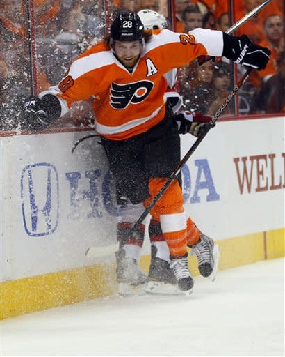 Philadelphia Flyers' Claude Giroux checks New Jersey Devils' Andy Greene into the boards during the second period in Game 2 of an NHL hockey Stanley Cup second-round playoff series, Tuesday, May 1, 2012, in Philadelphia. (AP Photo/Tom Mihalek)