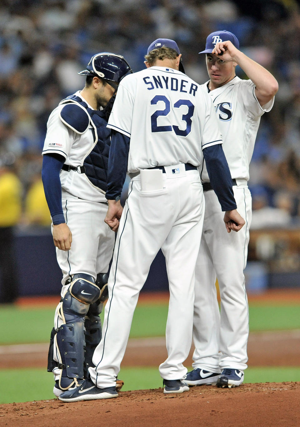 Tampa Bay Rays catcher Travis d'Arnaud, left, and pitching coach Kyle Snyder (23) talk with starter Brenda McKay on the mound during the second inning of a baseball game against the Chicago White Sox, Friday, July 19, 2019, in St. Petersburg, Fla. (AP Photo/Steve Nesius)