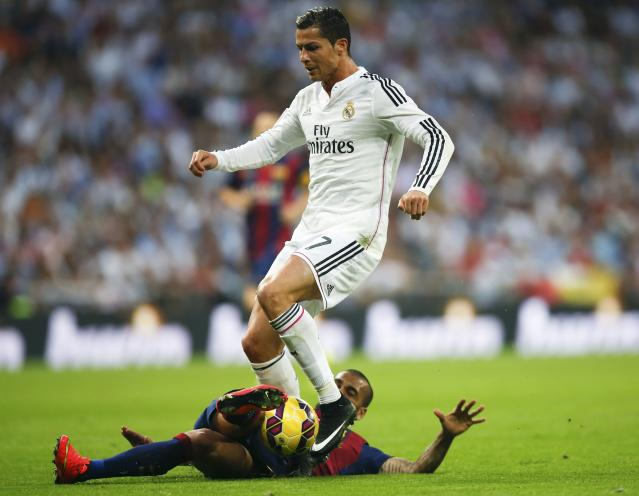 "Barcelona's Daniel Alves (bottom) tackles Real Madrid's Cristiano Ronaldo during their Spanish first division ""Clasico"" soccer match at the Santiago Bernabeu stadium in Madrid October 25, 2014. REUTERS/Sergio Perez (SPAIN - Tags: SOCCER SPORT)"