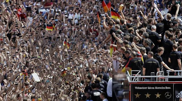 "10ThingstoSeeSports - Members of the German soccer squad wave to fans after the arrival of the German national soccer team in Berlin Tuesday, July 15, 2014. Germany's World Cup-winning team has returned home from Brazil to celebrate the country's fourth title with huge crowds of fans. The team's Boeing 747 touched down at Berlin's Tegel airport midmorning Tuesday after flying a lap of honor over the ""fan mile"" in front of the landmark Brandenburg Gate. (AP Photo/Michael Sohn, File)"