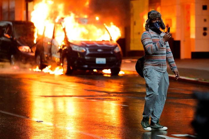 A person holds a phone and stands in front of burning vehicles following demonstrations protesting the death of George Floyd, a black man who died May 25 in the custody of Minneapolis Police, in Seattle, Washington on May 30, 2020.