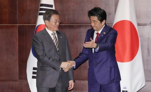 South Korea's President Moon Jae-in (L) shakes hands with Japan's Prime Minister Shinzo Abe (R) as the two met in Chengdu