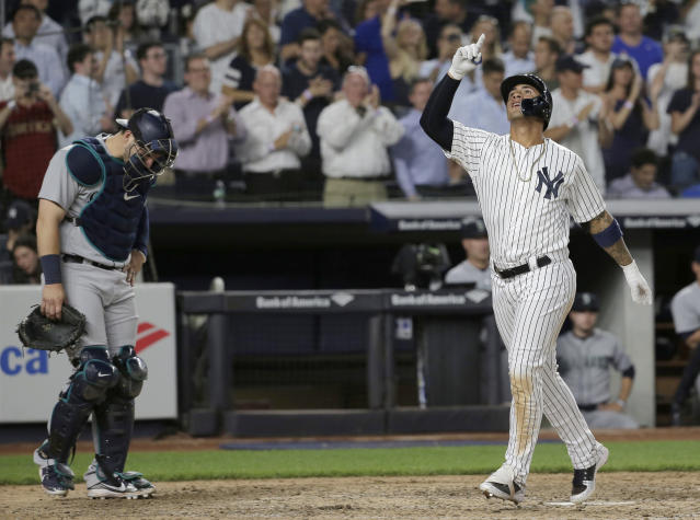 New York Yankees' Gleyber Torres, right, and Seattle Mariners catcher Mike Zunino react as Torres crosses home plate after hitting a home run during the eighth inning of a baseball game at Yankee Stadium Tuesday, June 19, 2018, in New York. (AP Photo/Seth Wenig)