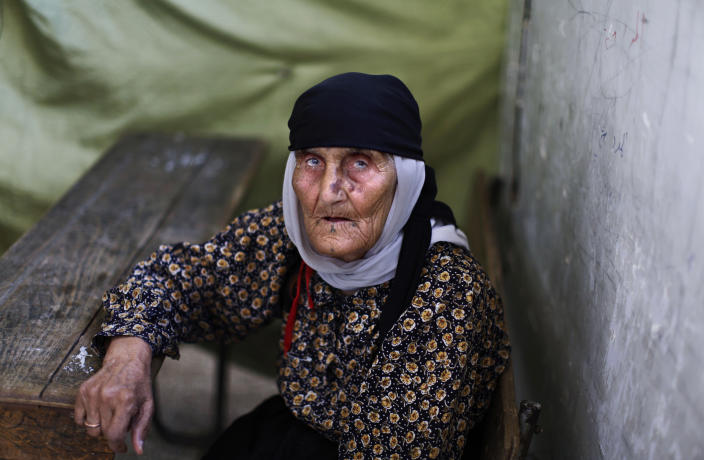 FILE - In this Sunday, Aug. 26, 2012 file photo, Fatimah Ali, an elderly Syrian who fled her home in Aleppo with her family due to fighting between the rebels and the Syrian army, rests at a desk in a school where she and her family took refuge in Suran, Syria. As sectarian slayings have swelled between Syria's Sunni majority and the Alawite minority during the country's 17-month-old conflict, so has the segregation of the two communities as they flee each other. (AP Photo/Muhammed Muheisen, File)