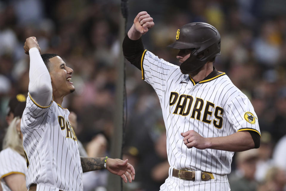 San Diego Padres' Wil Myers, right, is congratulated by Manny Machado after hitting a home run during the second inning of the team's baseball game against the Cincinnati Reds on Friday, June 18, 2021, in San Diego. (AP Photo/Derrick Tuskan)
