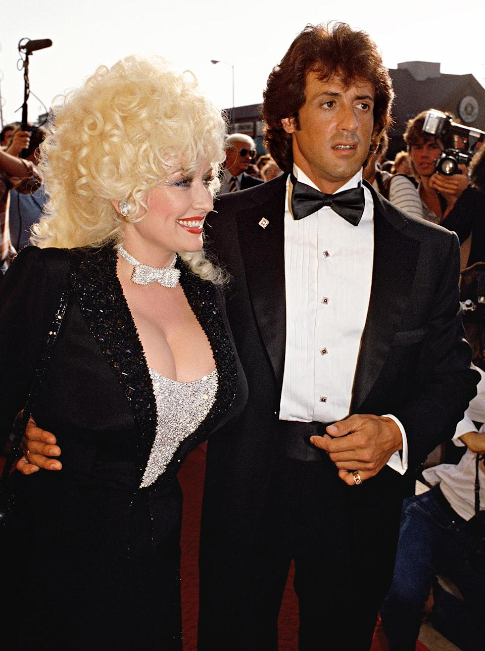 """<p>She knew costar Sylvester Stallone would be """"dressed to the nines"""" for the premiere of <em>Rhinestone Cowboy </em>in 1984<em>.</em> """"So I tried to look my Dolly best,"""" she said. And she succeeded in this crystal bustier top, matching bow-tie choker and embellished tuxedo jacket ensemble. </p>"""