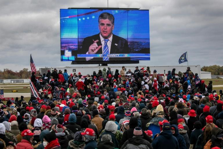 A large screen shows Fox News anchor Sean Hannity at a Trump rally in Waterford, Michigan on October 30, 2020