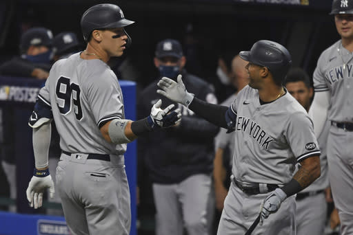 New York Yankees' Aaron Judge (99) is congratulated by Aaron Hicks after hitting a two-run home run off Cleveland Indians starting pitcher Shane Bieber (57) in the first inning of Game 1 of an American League wild-card baseball series, Tuesday, Sept. 29, 2020, in Cleveland. (AP Photo/David Dermer)