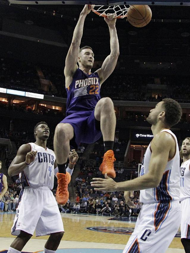 Phoenix Suns' Miles Plumlee, center, dunks as Charlotte Bobcats' Jeff Adrien, left, and Jeff Taylor, right, stand by during the first half of an NBA basketball game in Charlotte, N.C., Friday, Nov. 22, 2013. (AP Photo/Chuck Burton)