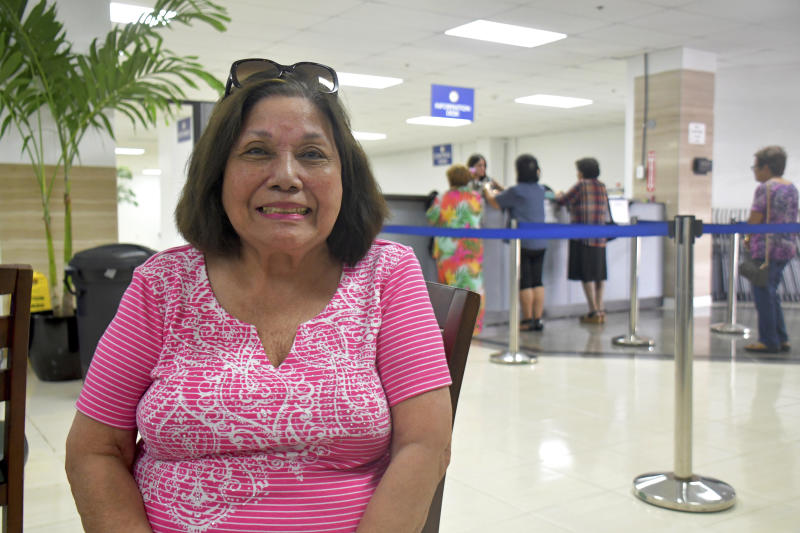 In this Friday, Feb. 7, 2020 photo, Antonina Palomo Cross, 85, sits at the Guam war claims office in Tamuning, Guam after getting confirmation that she will receive a payment for her experience living through the Japanese occupation of the U.S. Pacific island territory in 1941. The 1941 Japanese invasion of Guam, which happened on the same December day as the attack on Hawaii's Pearl Harbor, set off years of forced labor, internment, torture, rape and beheadings.  Now, more than 75 years later, thousands of people on Guam, a U.S. territory, are expecting to get long-awaited compensation for their suffering at the hands of imperial Japan during World War II. (AP Photo/Anita Hofschneider)
