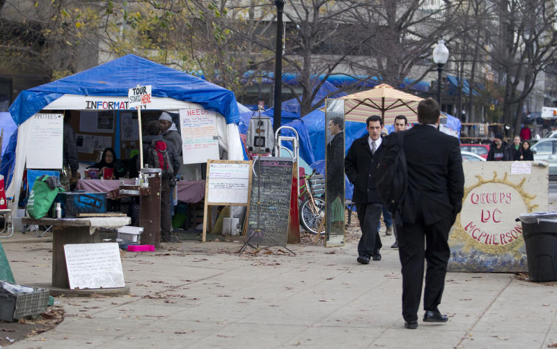 FILE - In this Dec. 5, 2011 file photo, Occupy DC protesters watch morning commuters walk through McPherson Square in Washington. The income gap between the rich and everyone else is large and getting larger, while middle-class incomes stagnate. That's raised concerns that the nation's middle class isn't sharing in economic growth as it has in the past. And it sparked the Wall Street protests that spread to other cities in the country.   (AP Photo/Evan Vucci, File)