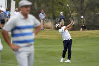 Antoine Rozner, of France, playing against Bryson DeChambeau, left, hits his second shot on the 13th hole, during a first round match at the Dell Technologies Match Play Championship golf tournament Wednesday, March 24, 2021, in Austin, Texas. (AP Photo/David J. Phillip)