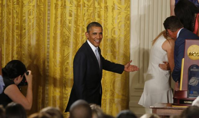 U.S. President Barack Obama gestures back towards UConn women's basketball star Stefanie Dolson (R) as she hides her face after falling off the stage during a ceremony honoring the NCAA basketball champion University of Connecticut Huskies men's and women's basketball teams in the East Room of the White House in Washington, June 9, 2014. Dolson was uninjured in the fall. REUTERS/Jim Bourg (UNITED STATES - Tags: POLITICS SPORT BASKETBALL)