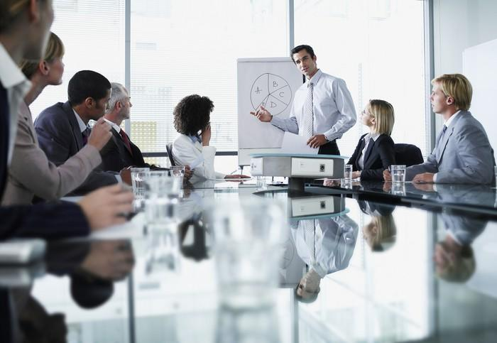 A man leads a presentation around a table in an office setting.