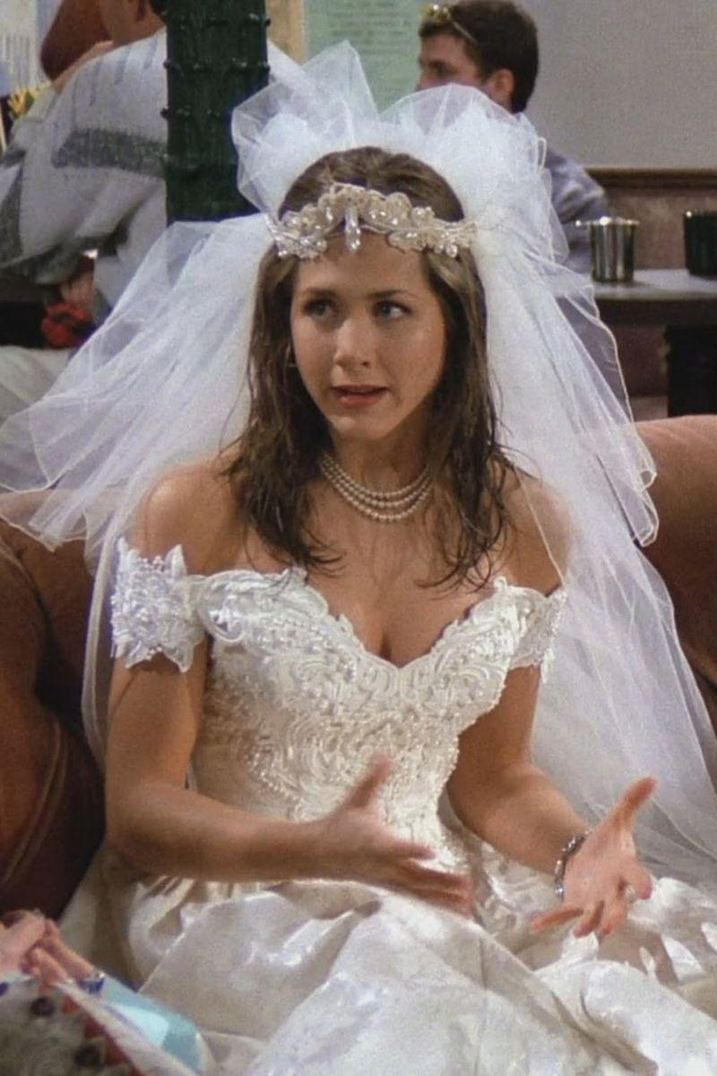 """<p>Although she ran away from her wedding, Rachel wearing her dress on the Central Perk sofa was an iconic moment from the sitcom's pilot episode. Her off-the-shoulder dress with lace applique was surprisingly chic, and she accessorized with a three-strand pearl necklace, a headband, and a tulle veil. The now-infamous dress was actually Warner Bros. stock from the <a href=""""https://www.racked.com/2017/6/7/15742358/friends-tv-show-weddings"""" rel=""""nofollow noopener"""" target=""""_blank"""" data-ylk=""""slk:costume department"""" class=""""link rapid-noclick-resp"""">costume department</a>.</p>"""