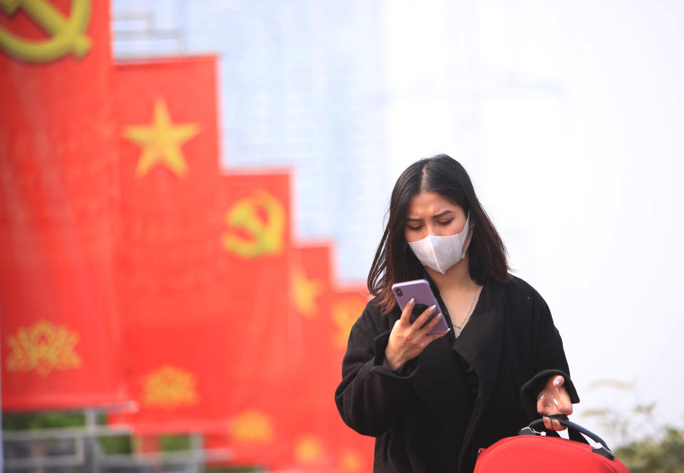 FILE - In this Jan. 23, 2021 file photo, a woman wearing face mask looks at her phone in Hanoi, Vietnam. Vietnam says it has discovered a new coronavirus variant that's a hybrid of strains first found in India and the U.K. The Vietnamese health minister made the announcement Saturday, May 29. (AP Photo/Hau Dinh, File)