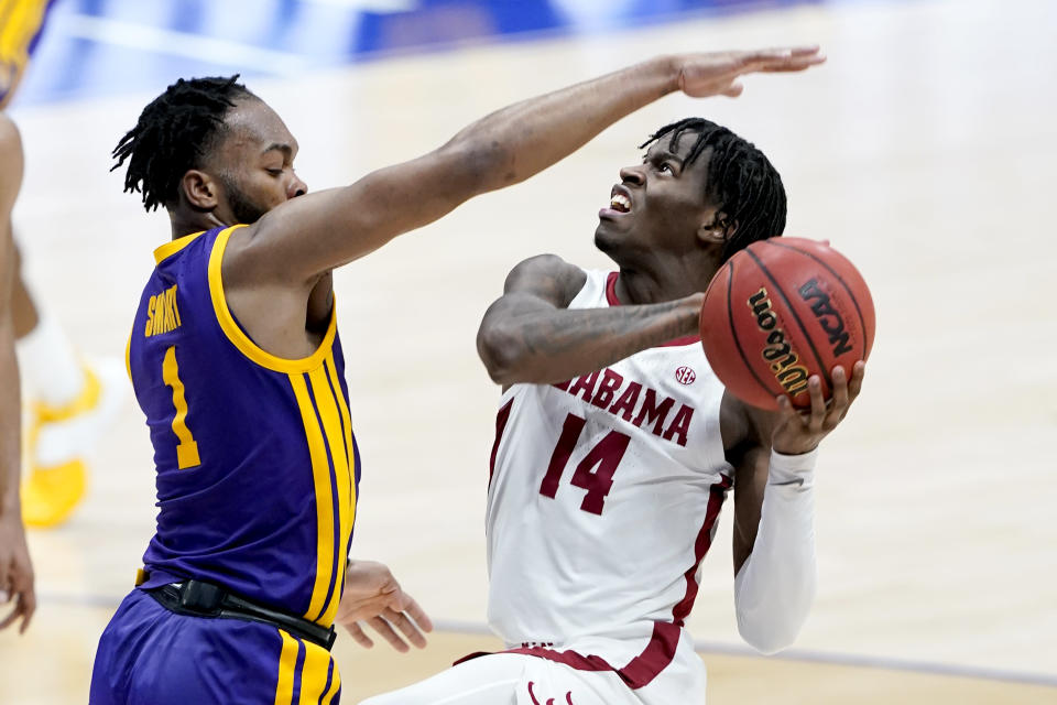 Alabama's Keon Ellis (14) drives against LSU's Ja'Vonte Smart (1) during the first half of the championship game at the NCAA college basketball Southeastern Conference Tournament Sunday, March 14, 2021, in Nashville, Tenn. (AP Photo/Mark Humphrey)