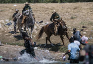 U.S. Customs and Border Protection mounted officers attempt to contain migrants as they cross the Rio Grande from Ciudad Acuña, Mexico, into Del Rio, Texas, Sunday, Sept. 19, 2021. (AP Photo/Felix Marquez)
